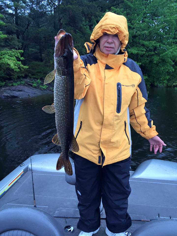 Wanda Fey Mahr with Northern Pike during a French River Rainy Day with her yellow rain jacket