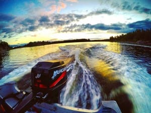Action shot of a boat Mercury Motor in motion on the French River Delta, evening sunset photo