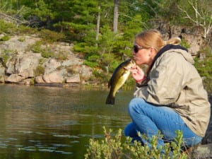 Woman kissing a French River smallmouth bass