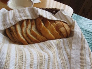 Crusty sliced italian white bread fresh from the oven in a basket ready to serve.
