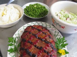An assortment of fresh herbs and vegetables prepared with a classic italian meatloaf.