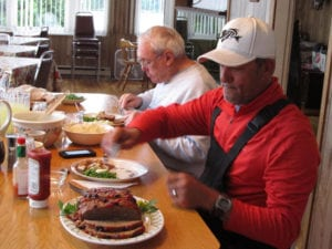 Family style diner with two fishermen eating home cooked meatloaf, real mash potatoes, and garden fresh peas.