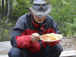 A man enjoying his French River Walleye Shore lunch while Fishing from Bear's Den Lodge