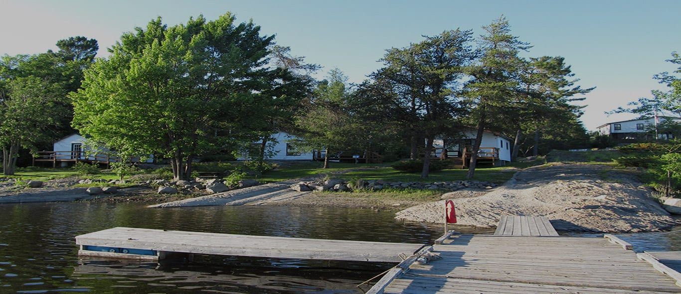 Image of the front of the Bear's Den Lodge, waterside view of the French River Delta and docking area