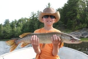 Northeastern Ontario Northern Pike Fishing with a Boy in orange shirt holding a nice sized Fish