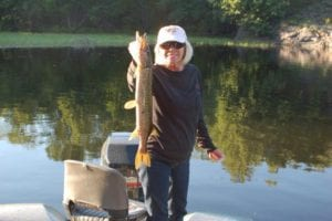 Wanda Fay Mahr fishing on the French River Delta, holding a Northern Pike