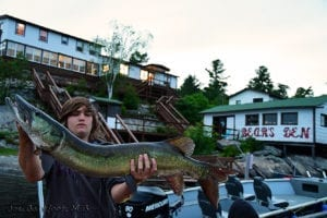 Mathias holding a 46 inch Musky with Bear's Den Lodge in background